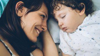 Mutti schaut Kind beim Schlafen zu