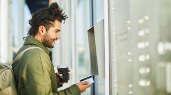 Mann steht mit Bankkarte vor Automat