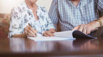 Älteres Ehepaar unterschreibt Vertrag