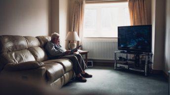 Rentner sitzt vor großem Fernseher