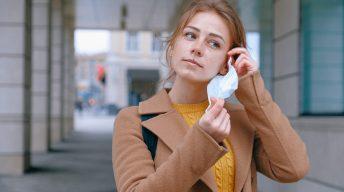 Frau nimmt Mund-Nasen-Bedeckung ab