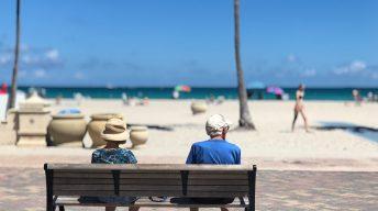 Zwei Leute auf einer Bank bei Strand und Meer
