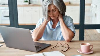 Frau massiert sich den Nacken vor Laptop