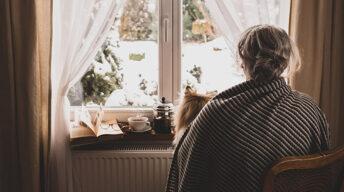 Einsamkeit Frau schaut aus Fenster