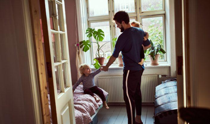Vater mit Kindern im Zimmer