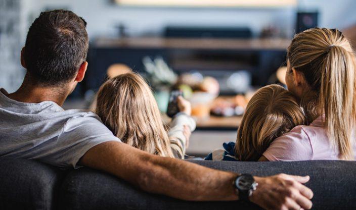 Familie sitzt auf der Couch und schaut fern