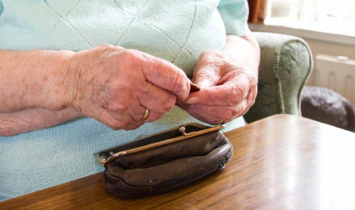 Alte Frau zählt Kleingeld