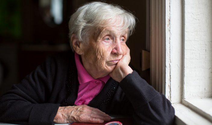 Rentnerin schaut aus Fenster