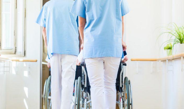 Pfleger schieben zwei Rollstühle