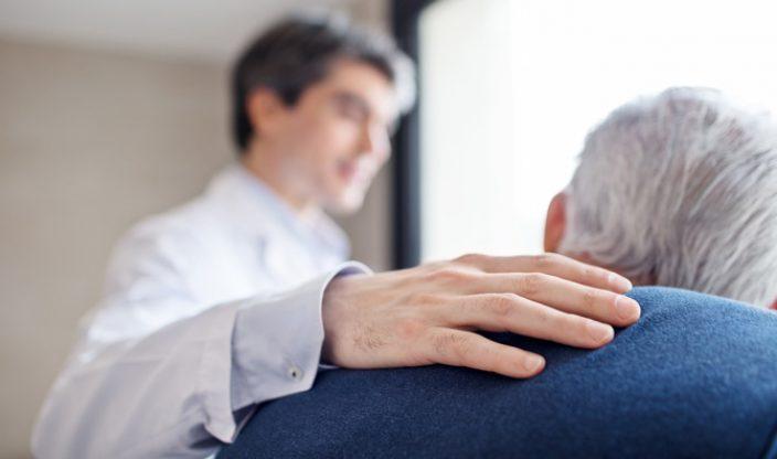 Mann legt Älterem die Hand auf die Schulter