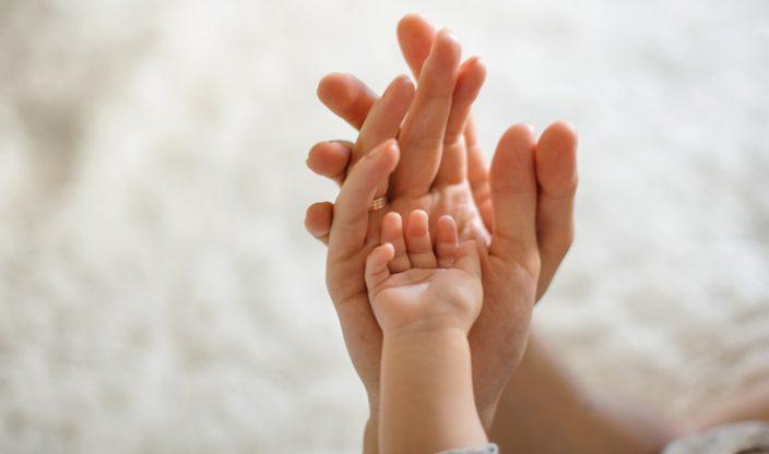 Hände von Eltern und Baby
