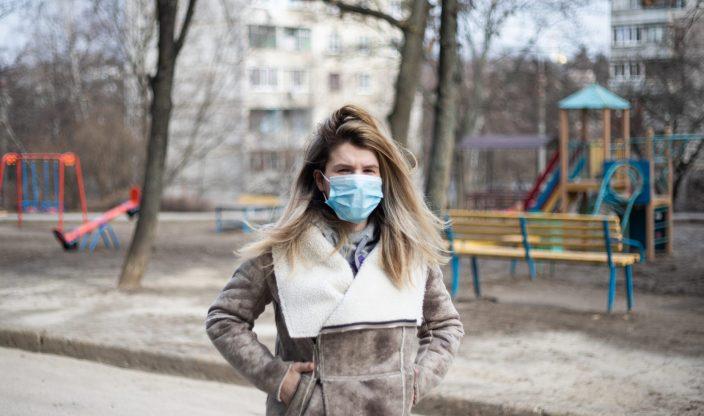 Frau mit Maske vor Spielplatz