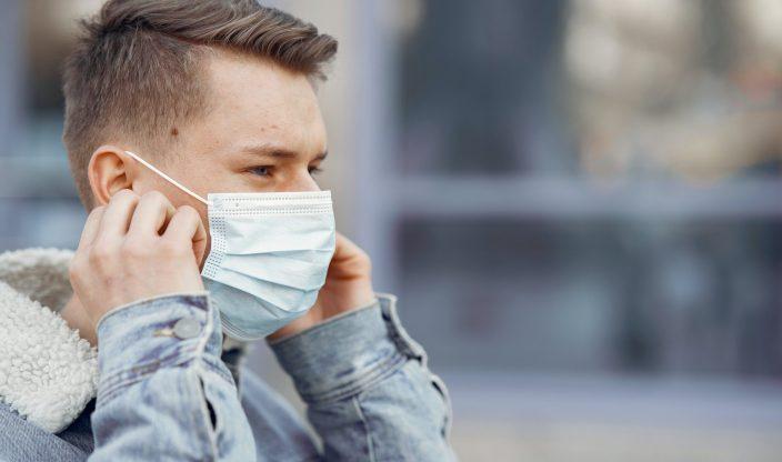 Mann setzt Atemschutzmaske auf