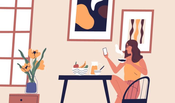 Frau am Tisch schaut aufs Handy