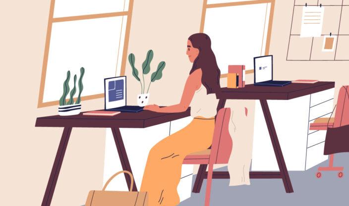 Frau sitzt am Schreibtisch und arbeitet