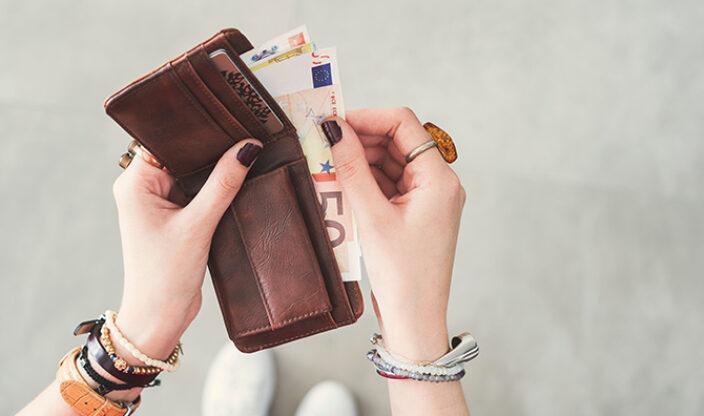Frau nimmt Geld aus Geldbörse