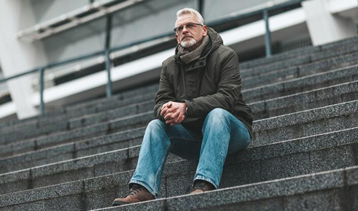 Mann sitzt auf einer Treppe